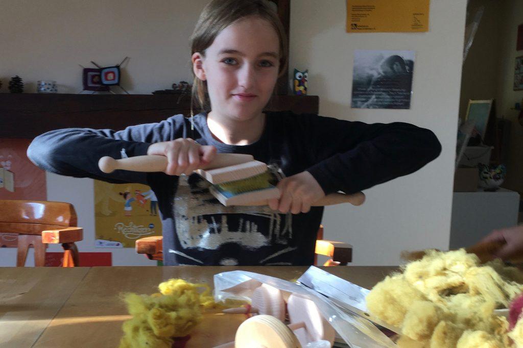 Johanna kämmt die gefärbte Wolle mit Handkarden.