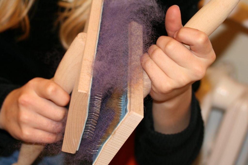 Die Fasern werden mit Handkarden gekämmt.